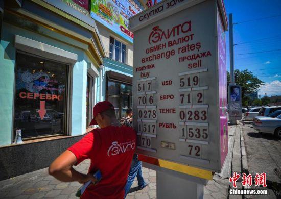 6月25日, 吉尔吉斯斯坦首都比什凯克街头一家外汇兑换点前的广告牌清晰的标明该店当天吉尔吉斯斯坦货币索姆兑换美元等外币的买入卖出价。刘新 摄