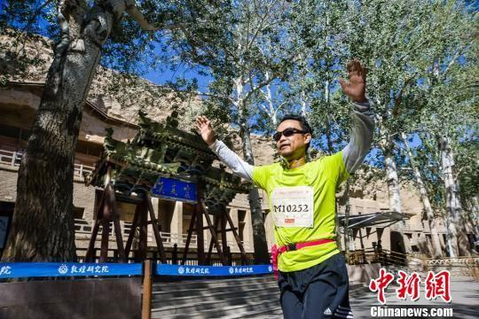 10月6日,2016丝绸之路敦煌国际马拉松赛6日在国际旅游名城甘肃敦煌鸣枪起跑。图为参赛选手抵达比赛终点——世界文化遗产敦煌莫高窟。 王斌银 摄