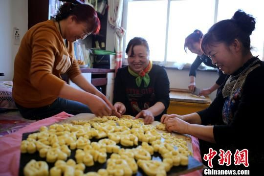 """春节临近,甘肃省张掖市甘州区农村,几户人家联合起来,用""""土烤炉""""做年馍馍、炸油果子,老人孩子齐上阵,为新春佳节做准备,充满浓浓的年味。图为村民自制的油果子。戴珊 摄"""