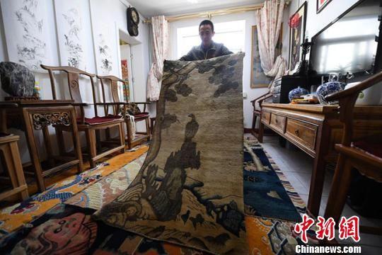 王选成展示收藏的古毯。 杨艳敏 摄