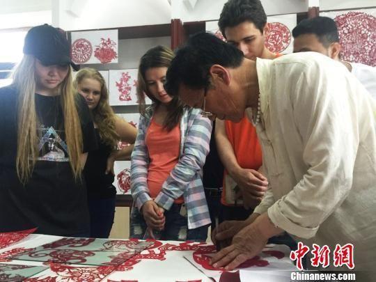 图为留学生参观陇中剪纸作品展。 杨娜 摄