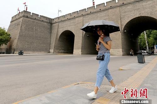 资料图:西安城墙下市民撑伞走过。 中新社记者 张远 摄