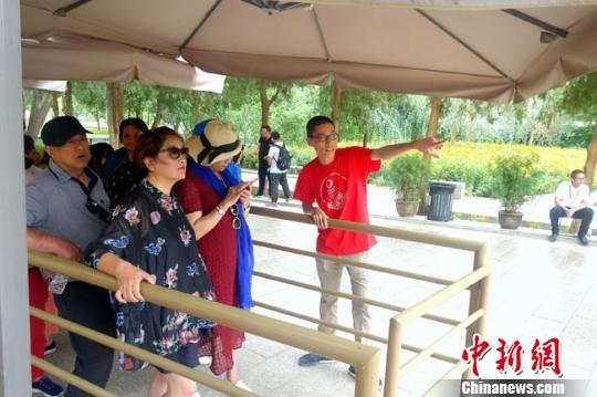 图为志愿者为等候参观的游客介绍莫高窟景区相关内容。 李文城 摄