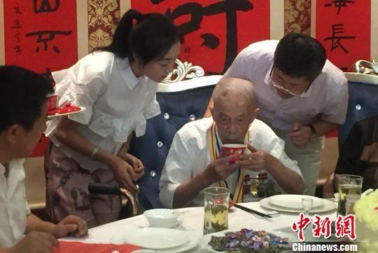 图为大家为老人敬茶。 刘玉桃 摄