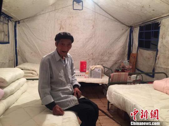 图为文县天池镇白马村受灾民众安置点帐篷内,90岁的老人王汝德独自坐着。床边放着挂面、矿泉水等救援物资。 南如卓玛 摄