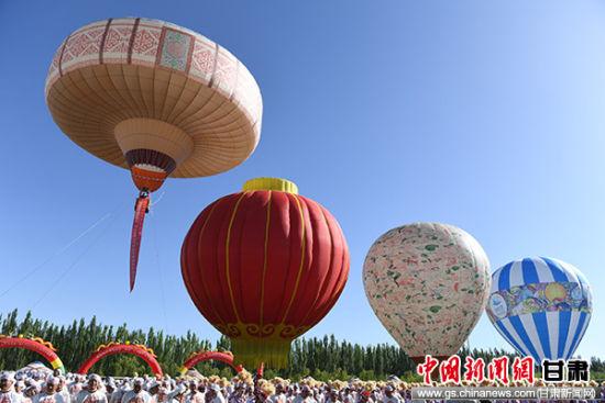 """8月12日,首届""""丝路蔚蓝(阿克塞)热气球嘉年华""""活动在甘肃酒泉市阿克塞县启幕。""""世界最大的哈萨克毡房热气球""""当日亮相(左一),并现场通过世界纪录协会认证。"""
