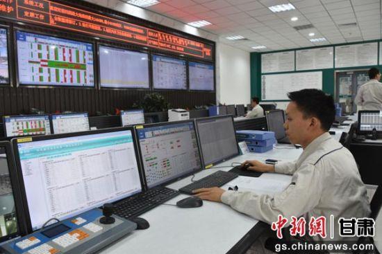 图为换流站工作人员监测设备运行情况。