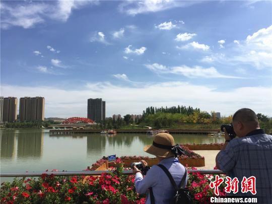 蓝天白云下的新区人工湖风景如画,吸引媒体代表拿起相机记录湖光潋滟的景色。 史静静 摄