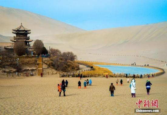 资料图:游客在国际旅游名城甘肃敦煌参观。图为敦煌月牙泉畔游人不绝。王斌银 摄