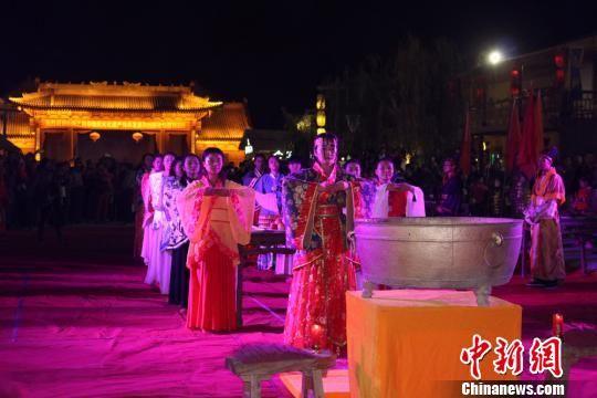 图为参祭女子手捧月饼及各式贡品,在皓月银辉中虔诚致祭。 吴莉 摄