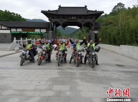 """郝学生(左一)与""""摩友""""骑摩托车去江苏省南云台山中麓,在花果山景区门前合影留念。 受访人提供"""