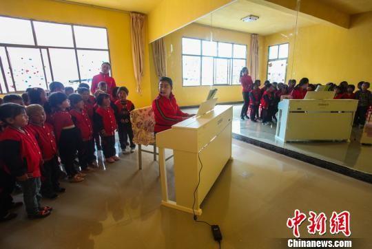 今年,武警官兵又为这所农村幼儿园配备钢琴。图为孩子们每周上一堂启蒙钢琴课。 钟欣 摄