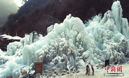 甘肃省积石山县大墩峡景区,冰挂美景吸引游人驻足留念。 史有东 摄