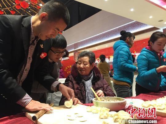 图为志愿者们在伊和园礼宴中心活动主现场包饺子。 钟欣 摄