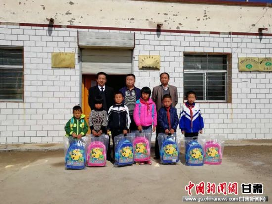 """农行在武威古浪县直滩乡十支村开展""""精准扶贫。关爱中小学生健康成长""""安全爱心包捐赠活动。"""