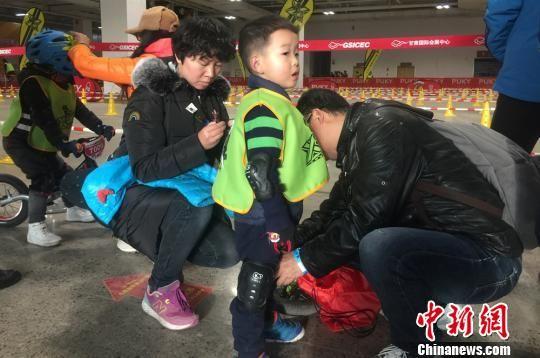 图为家长给小选手穿戴保护装备。 刘玉桃 摄