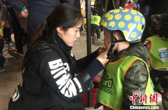图为家长给小选手带好头盔。 刘玉桃 摄