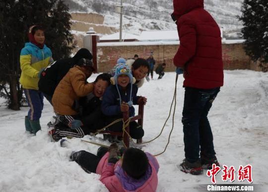 瓦天沟小学老师仿佛回到自己的孩童时光,图为老师和小学生们在课间痛痛快快得玩雪。 敬斐斐 摄