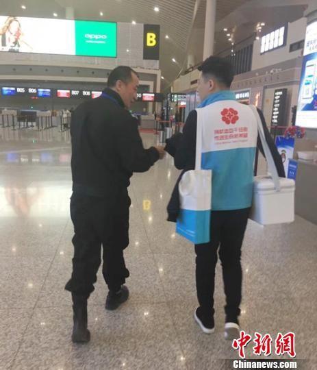 """图为甘肃省红十字会的工作人员刘江护送造血干细胞捐献者的160毫升""""生命种子""""赶赴广州的背影。 钟欣 摄"""