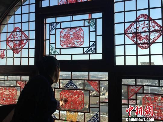 窑洞窗户是半圆形的,雕工精致的木条把窗户隔成一个个小方格。窗户上贴满剪纸,格外喜庆。 张婧 摄