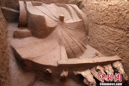资料图。图为甘肃马家塬战国墓地一墓葬内出土的车辆与伞。甘肃省文物考古研究所供图