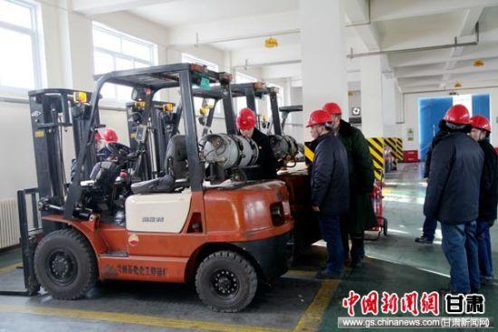 图为管理人员检查叉车安全状况确保节日生产畅通。