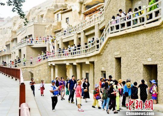资料图:丝绸之路上的国际旅游名城甘肃敦煌迎来了传统旅游旺季,敦煌莫高窟游人如织。 王斌银 摄