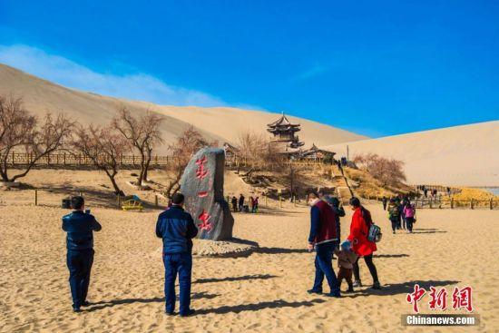 2月19日,游人在月牙泉畔体验丝路风情。 王斌银 摄