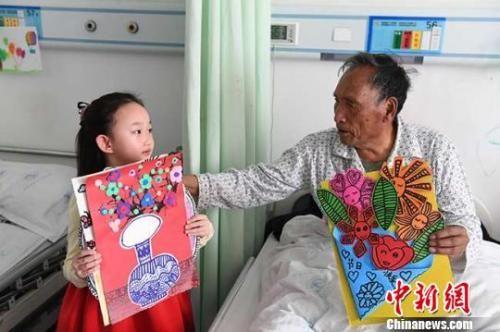 图为6岁的小女孩赵晋艺为病房里的老人送画。 杨艳敏 摄