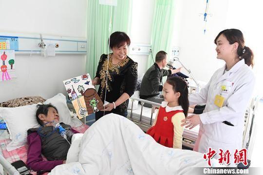 图为赵晋艺送完画站在老人床头小声说:奶奶,送您一幅画,给您贴床头,祝您早点好起来。 杨艳敏 摄