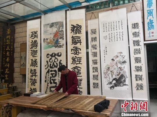 图为陈世三在博物馆内的工作台上摆放自己的木雕作品《百家姓》。 杨娜 摄