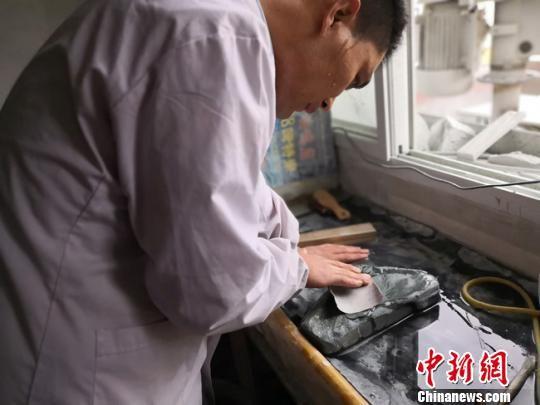 近日,在兰州大沙坪上川村,甘肃洮砚艺人黄炳强在自己的工作室里埋头雕刻。 杨娜 摄