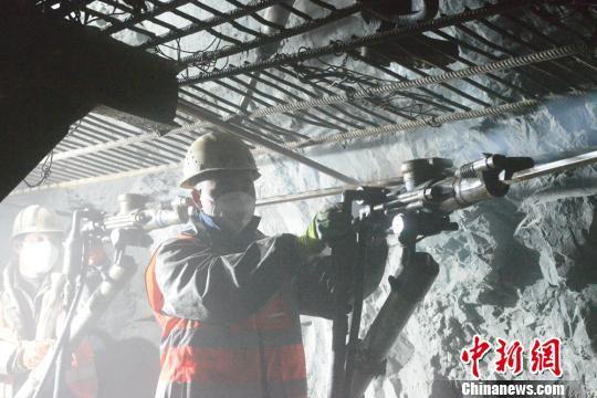 图为中铁十七局集团敦格项目当金山隧道内工人进行爆破钻孔作业。 张雷 摄