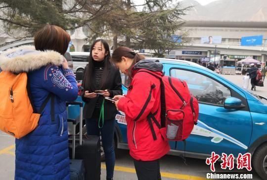 图为游客手机下载APP租车。 刘玉桃 摄
