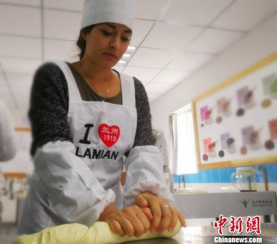 因为从小向往中国文化和美食,意大利女孩莉莉专程来到兰州牛肉面大学堂拜师学拉面。图为莉莉揉面。 史静静 摄