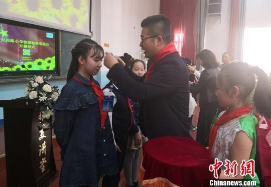 """图为安西路小学给学生发放电视台相关证件,学生今后可""""持证上岗""""。 刘玉桃 摄"""