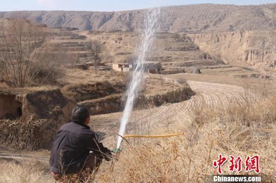 """资料图。早在2013年初,刘善忠看着村里荒废多年的土地,有了""""荒地变林地""""的想法,既能绿化荒山,又有创收效益。图为刘善忠检查浇树的水管。 张俊海 摄"""
