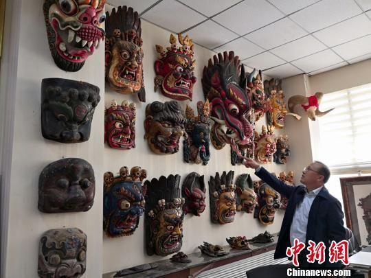 图为贾森栋和他收藏的傩面具。 刘薛梅 摄