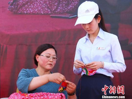 """4月19日,在甘肃庆阳市举办的""""小崆峒旅游文化节""""上,当地民间手工艺传承人在向游客教授剪纸技艺。 陈飞 摄"""