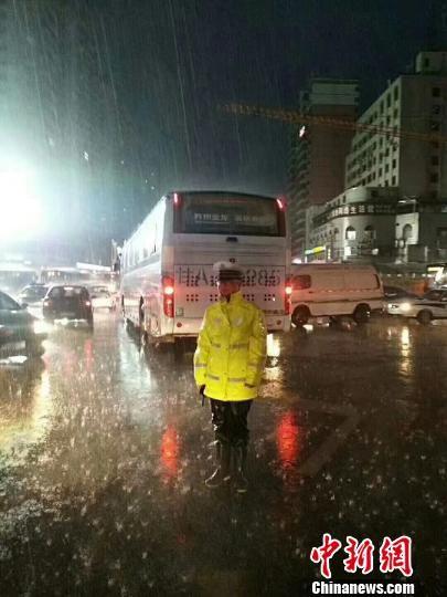 图为兰州交警在雨中疏导,确保路面交通秩序畅通。 钟欣 摄