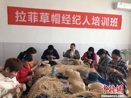 图为巧手代表正在学习编织拉菲草帽。 徐雪 摄