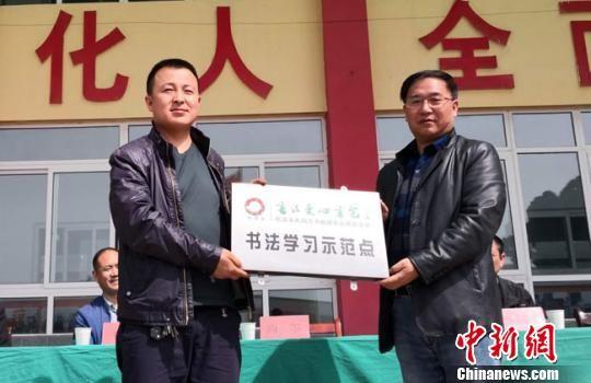 """4月26日,""""恒基金""""副理事长尚墨为甘谷永安伏羲学校授牌,这里将作为该基金会的书法学习示范点。 殷春永 摄"""