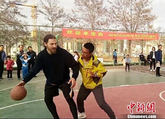 4月30日下午,欧美国际职业球员在甘肃定西市体育公园篮球场与当地球迷互动。 闫姣 摄
