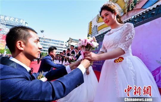 集体婚礼现场新郎单膝跪地向新娘献上鲜花。 王将 摄