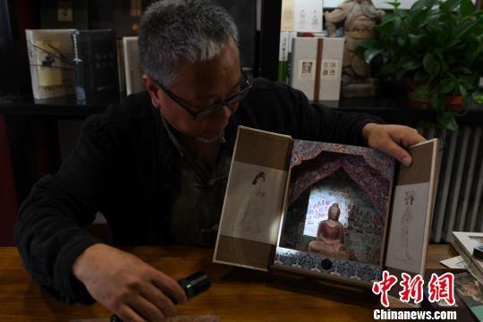 图为展现敦煌莫高窟佛窟的手工创意书。(资料图) 杨艳敏 摄