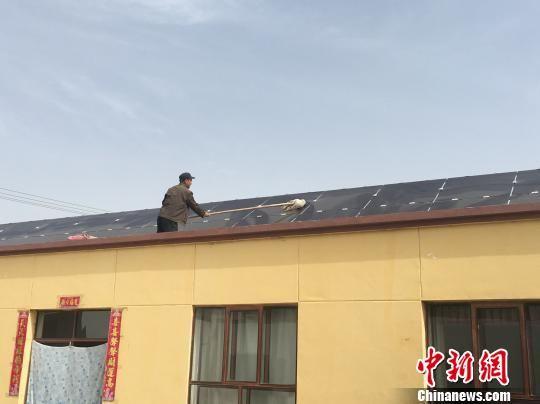 甘肃酒泉市瓜州县广至藏族乡新堡村,村民芦满财在自家的屋顶擦拭光伏电板。 张婧 摄