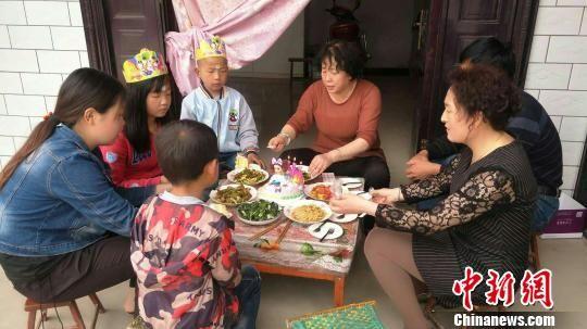 图为爱心妈妈团成员给孤儿过生日。 钟欣 摄