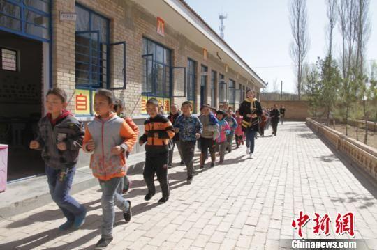 """图为""""90后""""教师武月带领学生跑步。 李文 摄"""