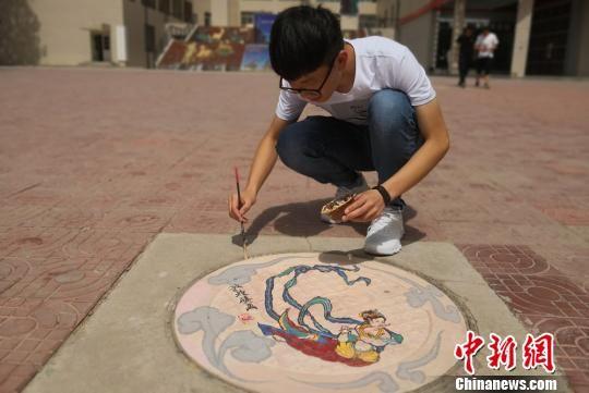 图为学生在井盖作画。 刘玉桃 摄