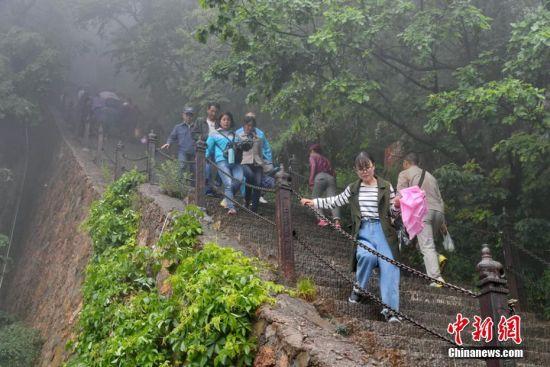 宛若仙境的美景和免票、优惠的政策吸引游客雨中登山赏景。